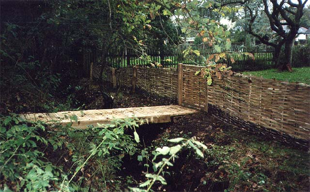 <span>Ref: B2</span><br>Here you see the reverse side of the cleft hazel panel, with a matching gate leading to an oak bridge.
