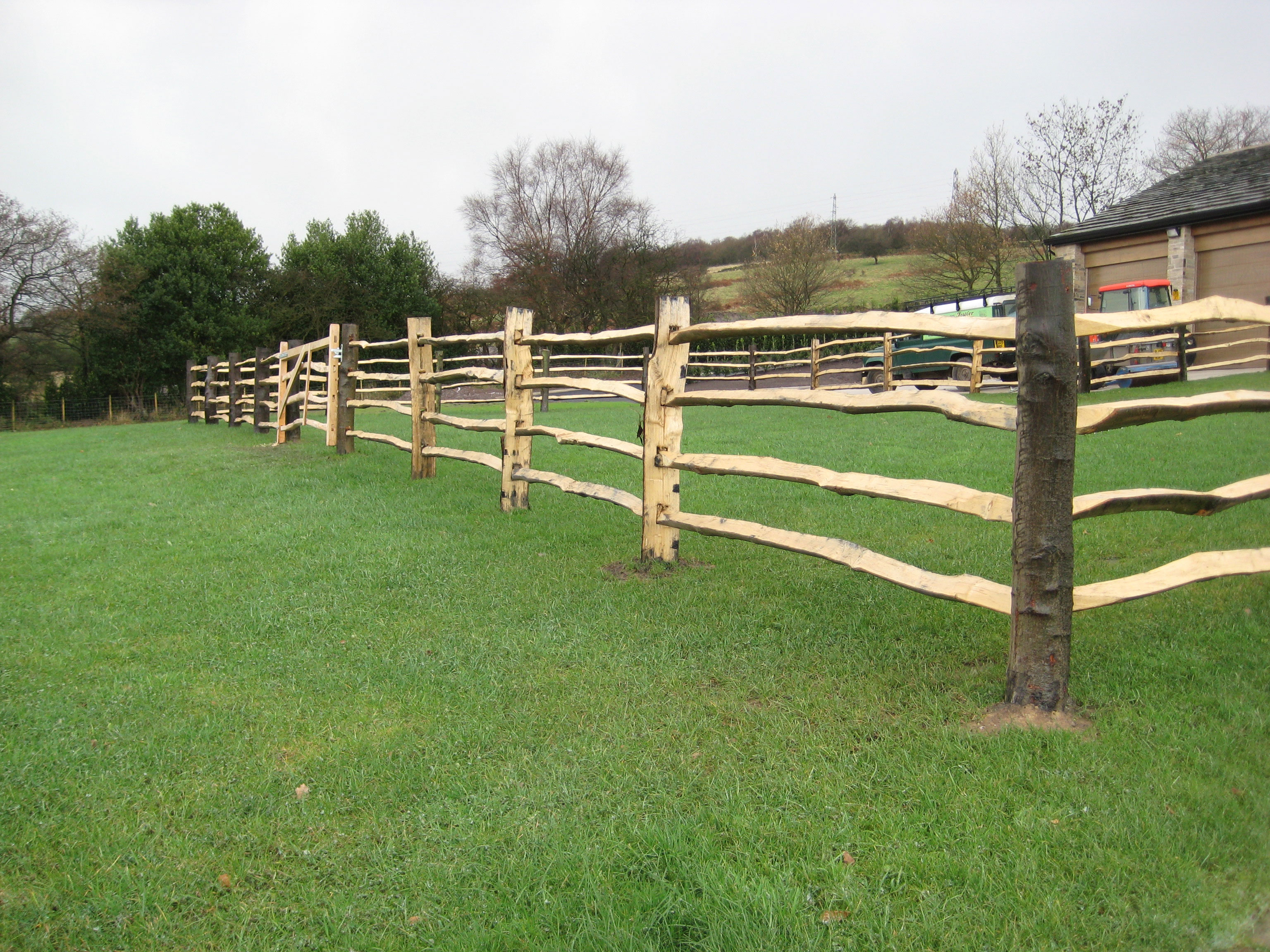 <span>Ref: A6</span><br>Cleft chestnut paddock fence with four rails. Note the round corner posts. Top rail at 4', materials approx £25.56/metre inc. VAT