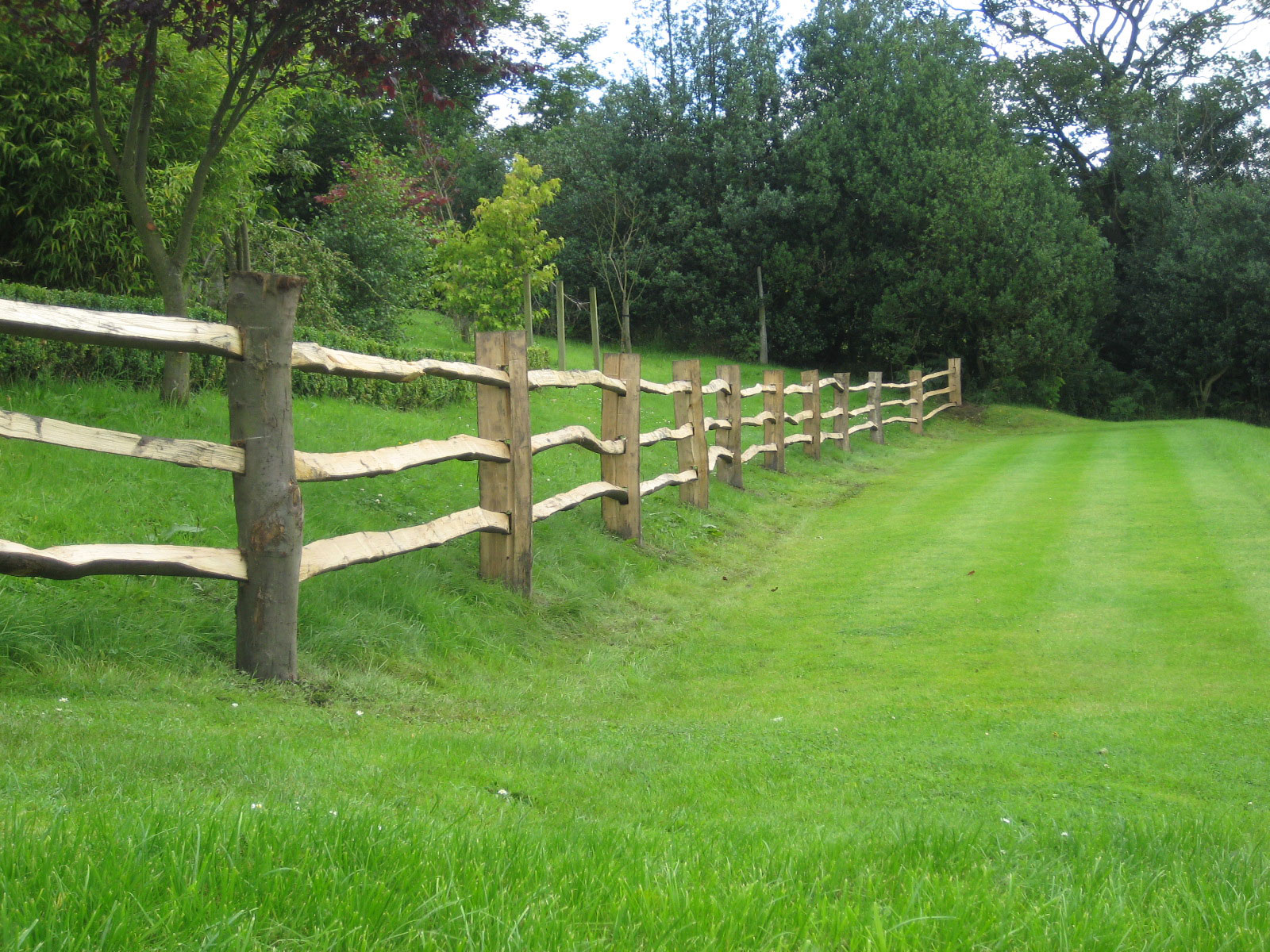 <span>Ref: A7</span><br>This riven chestnut fence delineates this orchard with style. Top rail at 4', materials approx £20.15/metre inc. VAT