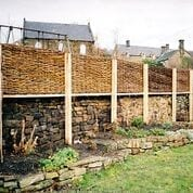 <span>Ref: B16</span><br>Tall willow hurdles supported on sawn chestnut posts, give seclusion whilst matching the background wall texture.