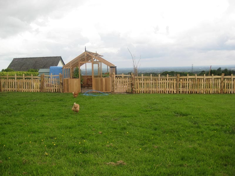 <span>Ref: A31</span><br>This cleft medieval deer park style fence fits nicely with the new cedar greenhouse, and it keeps the chickens off the vegetable garden, Lyme Park, Cheshire; materials approx £39.44/metre inc. VAT