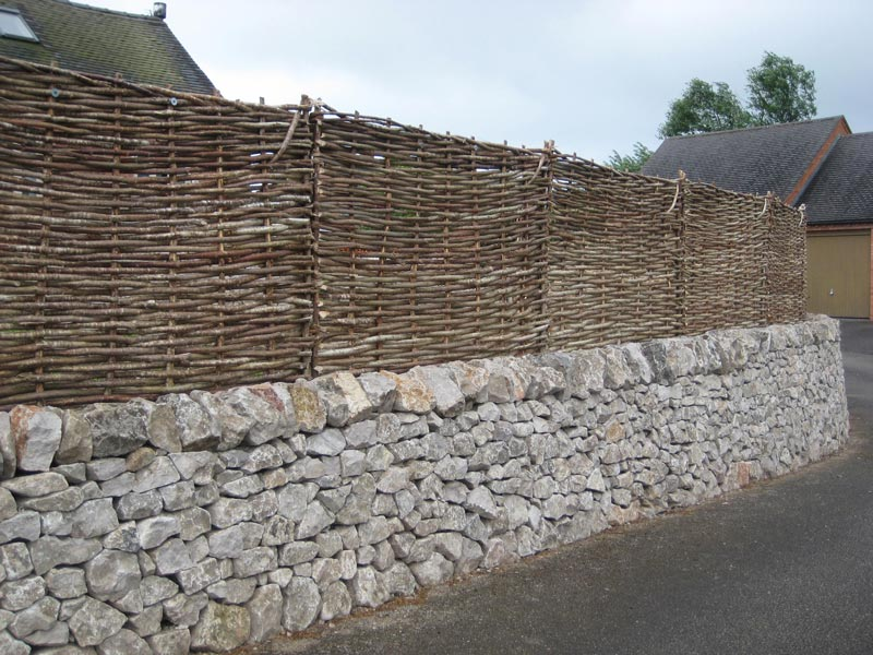<span>Ref: B7</span><br>These 4' high hazel hurdles enclose this raised garden giving privacy and matching the texture of the drystone wall.